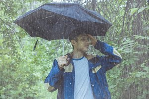 portrait of elegant handsome bearded man with umbrella in tropical rainforest during heavy rain