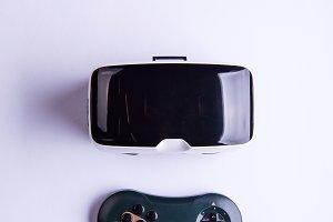 Virtual reality goggles and gamepad on table, studio shot