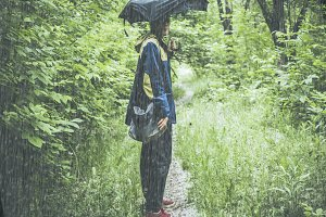 man in overcoat with umbrella and bag hiking the mountain in the forest on the path