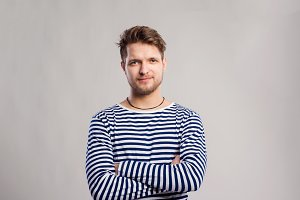 Hipster man in striped t-shirt, gray background, studio shot