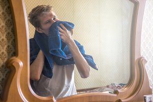 young bearded man in front of the mirror with towel after shower