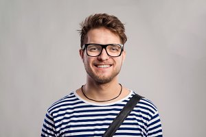 Man in striped t-shirt and eyeglasses against gray background.