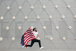 Happy hipster man with flag USA