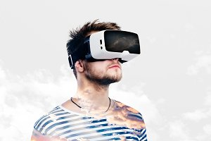 Double exposure. Man wearing virtual reality goggles. Sky and cl