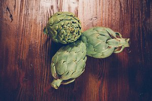 Artichokes on wooden table