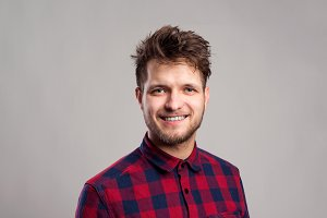 Hipster man in checked shirt smiling, against gray background.