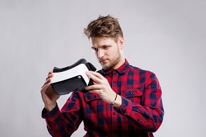 Man with virtual reality goggles. Studio shot, gray background