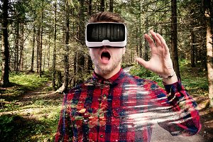 Man wearing virtual reality goggles. Green forest.