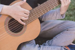 boy playing spanish guitar outdoors