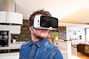 Man wearing virtual reality goggles. Home interior.