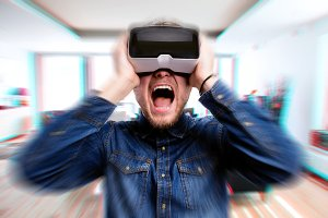 Man wearing virtual reality goggles screaming. Home interior.
