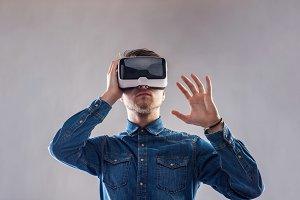 Man wearing virtual reality goggles. Studio shot, gray backgroun