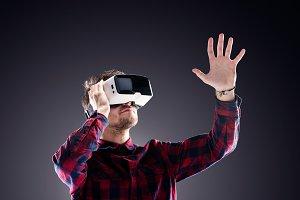 Man wearing virtual reality goggles. Studio shot, black backgrou