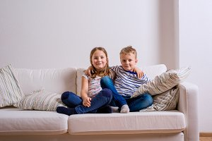 Boy and girl sitting on white couch. Copy space.