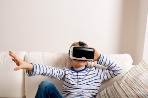 Boy wearing virtual reality goggles. Studio shot, white couch