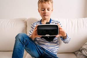 Boy with virtual reality goggles. Studio shot, white couch