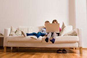 Children at home sitting on sofa, playing with laptop