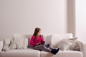 Girl at home sitting on sofa, playing with laptop