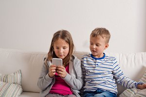 Children at home sitting on sofa, playing with smartphone