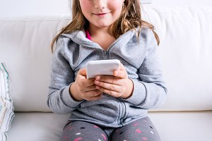 Unrecognizable little girl sitting on sofa, playing with smartph