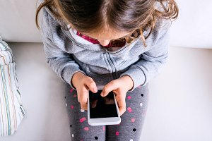 Little girl sitting on sofa, playing with smartphone