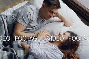 Cheerful caucasian man is lying in bed with his asian wife holding hands and talking, she is touching his hair and laughing. Mixed-race relationship and love concept.