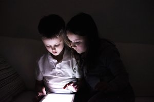 Two children, sitting in a dark, playing with tablet