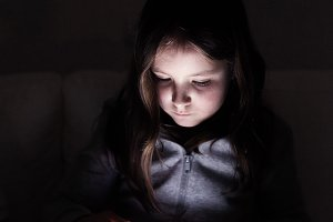 Little girl, sitting in a dark, playing with tablet