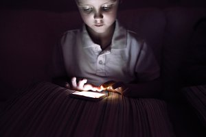 Little boy, sitting in a dark, playing with smartphone