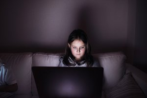 Little girl, sitting in a dark, playing with laptop