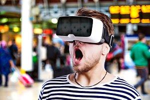 Man wearing virtual reality goggles standing at train station