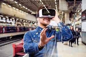Man wearing virtual reality goggles, standing at train station
