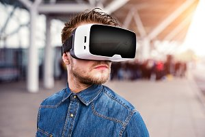 Man wearing virtual reality goggles standing at train station