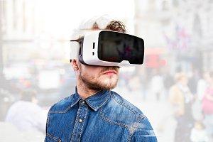 Man wearing virtual reality goggles. Studio shot, gray backgrou