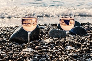 Two glasses of pink wine near sea