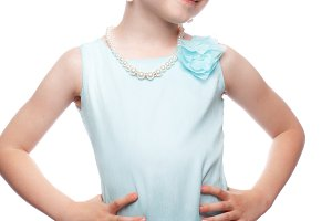A little girl in a blue dress, with a retro hairstyle and accessories.