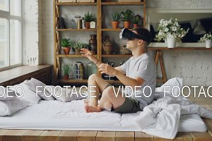 Excited young man is using augmented reality glasses moving hands while sitting on double bed in light apartment. Modern technology and happy people concept.