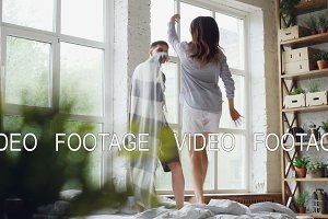 Cute couple is dancing on bed with blanket jumping and laughing together having fun on weekend morning in nice light apartment. Happy people and entertainment concept.