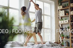 Young married couple is jumping and dancing on double bed in light room with large windows, happy people are&#