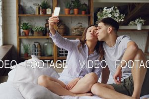 Cheerful loving couple is taking selfie with smartphone looking at camera, posing and making funny faces while sitting together on bed at home. Technology and relationship concept.