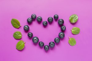 Blueberries laid out in the shape of a heart with mint leaves on bright crimson background