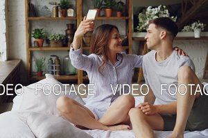 Funny young people boyfriend and girlfriend are taking selfie with silly faces having fun and kissing while sitting on bed at home. Self-portrait and rerlationship concept.