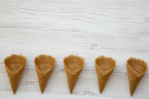 Waffle sweet cones on a white wooden