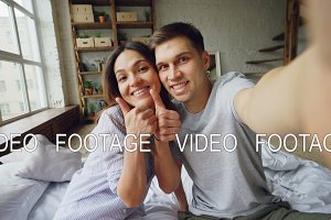 Point of view shot of loving couple taking selfie together posing, kissing and having fun while sitting on bed at home. Nice modern interior and large windows are visible.