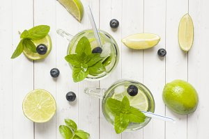 Fresh citrus Lemonade in a glass of lime berry mint blueberries on a light background.
