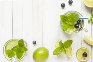 Fresh citrus Lemonade in a glass of lime berry mint blueberries on a light background. Copy space for text