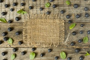 Blueberries and mint leaves on rustic wooden background Copy space for text