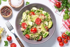 Quinoa salad with spinach, avocado and tomatoes top view.