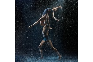 Young couple of ballet dancers dancing unde rwater drops