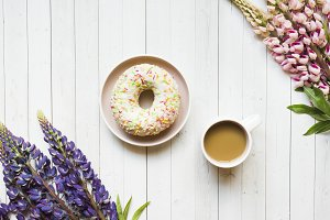 Still life with a Cup of coffee and lupine flowers donut on a light wooden table. Copy space